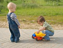 Children with a toy truck. Two boys trying to repair a toy truck Stock Image