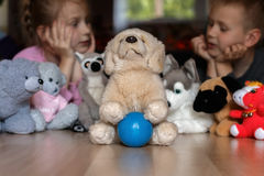 Children and toys. Children and soft toys on a wooden floor Royalty Free Stock Image
