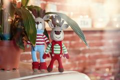 Two stylish amigurumi deers in striped sweaters, scarf and butterfly tie standing near flowerpot. Children toys. Two stylish amigurumi deers in striped sweaters royalty free stock images