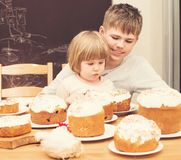 Children with traditional Easter homemade cakes and colored eggs. Teen boy and little girl sitting at the table full of. Traditional Easter cakes. Easter stock images