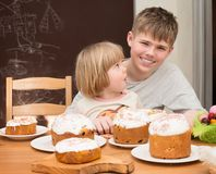 Children with traditional Easter homemade cakes and colored eggs. Teen boy and little girl sitting at the table full of. Traditional Easter cakes. Easter royalty free stock image