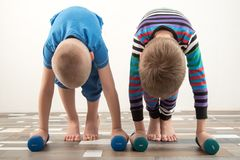 Children train with dumbbells. The concept of sport in the family.  Stock Photo