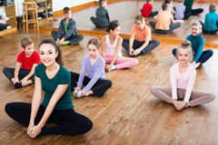 Children with trainer stretching Royalty Free Stock Photos