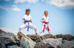 Children training karate on the stone coast. Against sky stock image