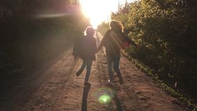 Children travelers. Hiker Girl. happy girls travelers with backpacks run along country road holding hands in rays of the