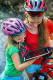 Children traveling bicycle in summer park. Bicyclist watch on tablet computer. Stock Photos