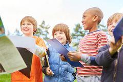 Children on a treasure hunt as a scavenger hunt. Happy children on a treasure hunt as a scavenger hunt in nature with clipboard stock photos
