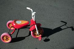 Children tricycle. Under direct sunlight with harsh shadow Royalty Free Stock Photo