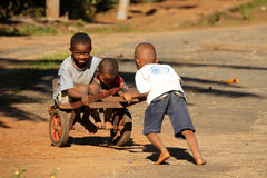Children with a trolley. African kids having fun and playing with old rusty trolley, Madagascar Stock Photo