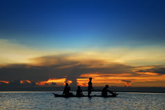Children in tropical canoe. Asian children's silhouette in a canoe at sea in front of a tropical flamboyant sunset Stock Photos