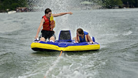 Children Tubing. A boy and girl riding a tube behind a boat being sprayed with water royalty free stock photos