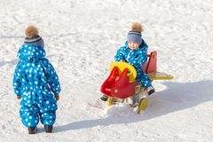 Children twin brothers walking in winter on Sunny day in matching jumpsuits Royalty Free Stock Image