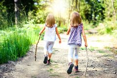 Children - twin girls are hiking in the mountains. Stock Photos