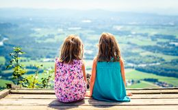 Children - twin girls sitting on paragliding ramp after hiking. Active family, parents and children mountaineering in the nature. Kids are resting and enjoying royalty free stock photo