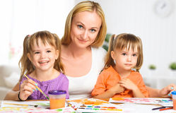 Children twin sisters draw paints with her mother in kindergarte Stock Photos