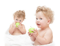 Children twins eating a green apple Royalty Free Stock Image