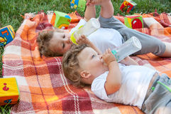 Children Twins Lay On The Coverlet Among The Toys And Drink Water From A Bottle Royalty Free Stock Photos