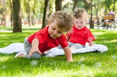 Children twins play on the grass. With soap bubbles Royalty Free Stock Photos