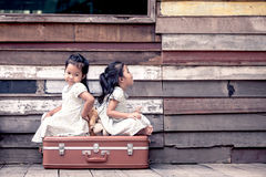 Children two cute asian little girls are sitting on suitcase stock photo