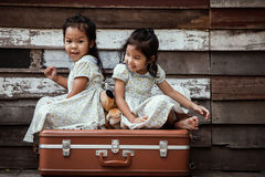 Children two cute asian little girls are sitting on suitcase Stock Photography