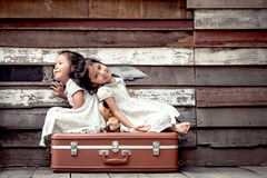 Children two cute asian little girls are sitting on suitcase Stock Image