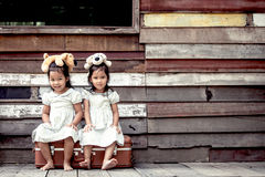 Children two cute asian little girls are sitting on suitcase Royalty Free Stock Photography