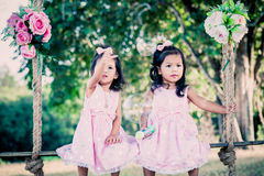 Children two cute little girls sitting on swing Stock Photography