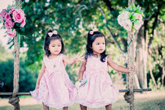 Children two cute little girls sitting on swing Royalty Free Stock Photos