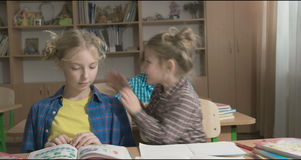 Children or two happy girls learning and doing homework in school classroom stock video footage