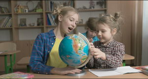 Children or two happy girls learning and doing homework in school classroom stock footage