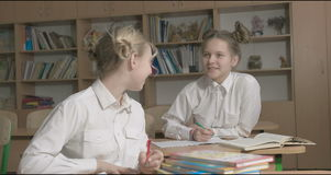 Children or two happy girls learning and doing homework in school classroom stock video