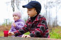 Children two little boy girl outdoor fall season. Children two little boy girl eat drink outdoor fall season Stock Image