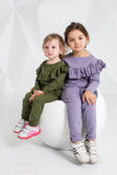 Children, two sisters 1.5 and 5 years old in the identical costumes of different colors, little girls on a white Royalty Free Stock Photos