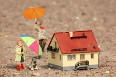Children with umbrellas, puppy and House model Royalty Free Stock Photos