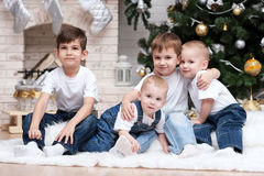 Children under the Christmas tree by the fireplace Royalty Free Stock Photo