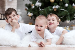 Children under the Christmas tree by the fireplace Royalty Free Stock Photos