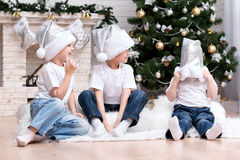 Children under the Christmas tree by the fireplace. Three little boys having fun at the Christmas Tree Royalty Free Stock Images
