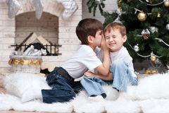 Children under the Christmas tree by the fireplace Royalty Free Stock Photography