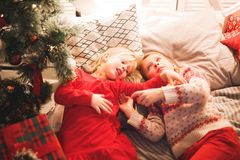 Children under Christmas tree with gift boxes. Decorated living room.  Royalty Free Stock Photo