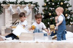 Children under the Christmas tree with gifts and toys. Children make out gifts at Christmas tree Royalty Free Stock Photos