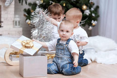 Children under the Christmas tree with gifts and toys. Children make out gifts at Christmas tree Royalty Free Stock Photography