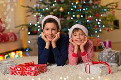 Children under Christmas tree. Happy kids laying on the floor in front of the Christmas tree Royalty Free Stock Image