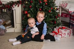 Children under the Christmas tree. Photo Christmas tree, fireplace, two boys brother Royalty Free Stock Image