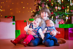 Children under a Christmas tree. Three happy children, brothers and sister sitting under a Christmas tree, boy holding a little toddler girl and funny baby, kids Stock Photos