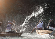 Children under the spray of water in the floating boats Stock Photos