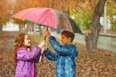 Children under umbrella enjoy to autumn rain Royalty Free Stock Image