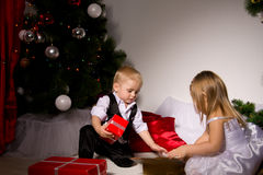 Children unpack gifts. Under the Christmas tree New Year's Eve Royalty Free Stock Image