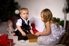Children unpack gifts. Under the Christmas tree New Year's Eve Stock Images