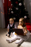 Children unpack gifts. Under the Christmas tree New Year's Eve Royalty Free Stock Photo