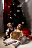 Children unpack gifts. Under the Christmas tree New Year's Eve Stock Photos